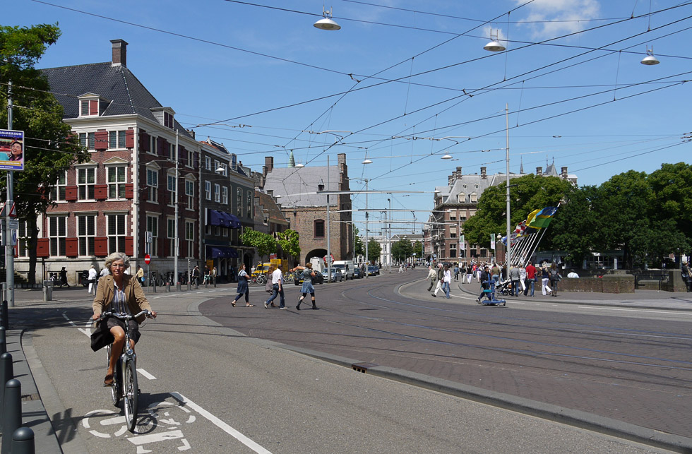 Гаага, улица с травваем и велосипедистка.