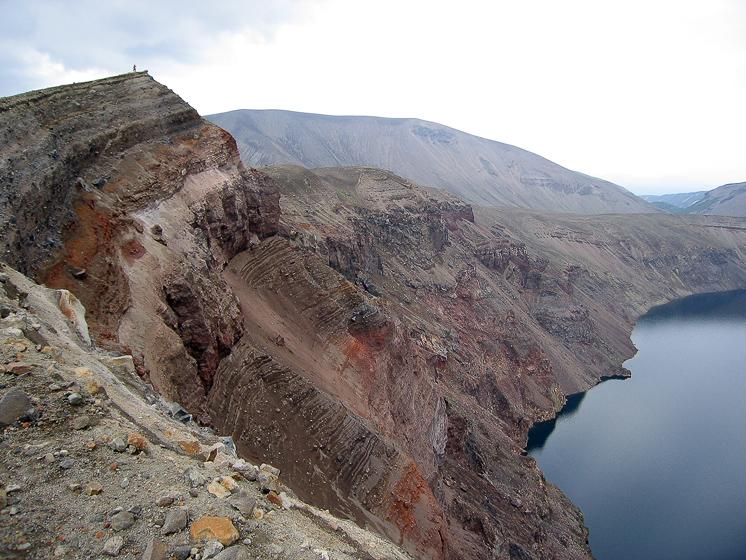 Кратер Штюбеля и Кратерное озеро. На вершине стоит человек. Ему сейчас кажется, что он может добросить камень до воды, но на самом деле он не сможет этого сделать.