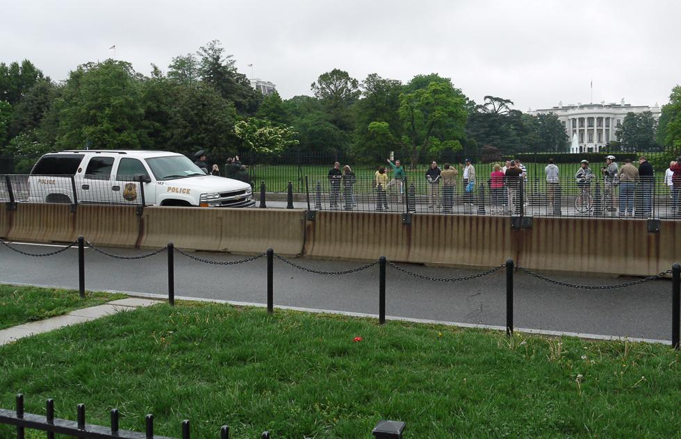 Вашингтон.  Пять разных ограждений и полицейский стоят на пути к лужайке перед Белым домом.