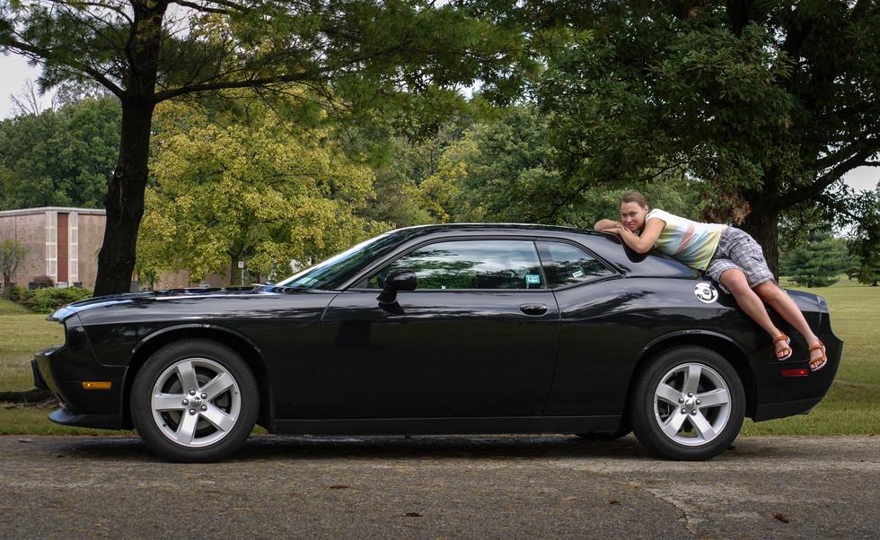 Девушка на черном Dodge Challenger, вид сбоку